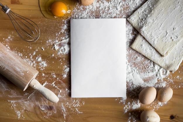 Tigela, ovos, farinha, gado ovo, rolo e casca de ovo em uma placa de madeira no topo
