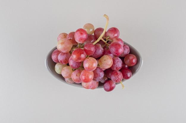 Tigela pequena com cacho de uva no mármore