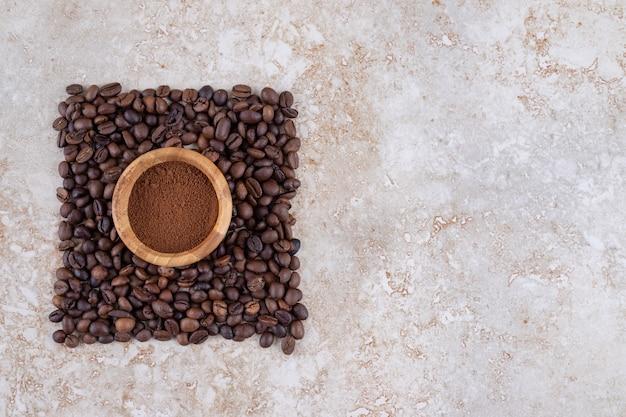 Tigela pequena com pó de café cercada por uma pequena pilha de grãos de café