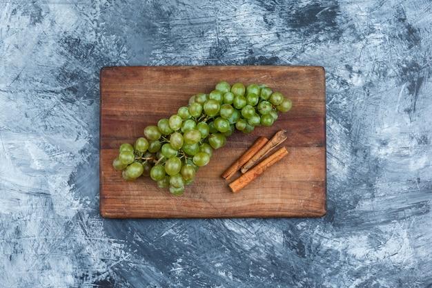 Tigela plana leiga de uvas, canela em uma tábua em fundo de mármore azul escuro. horizontal