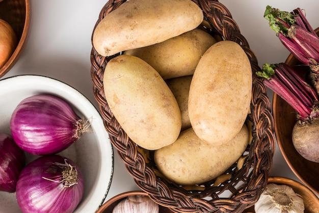 Tigela plana leiga e sacos com legumes