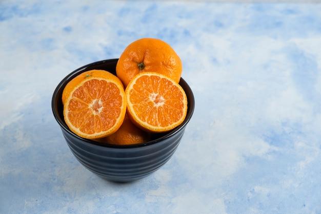 Tigela preta cheia com tangerinas cortadas inteiras ou pela metade