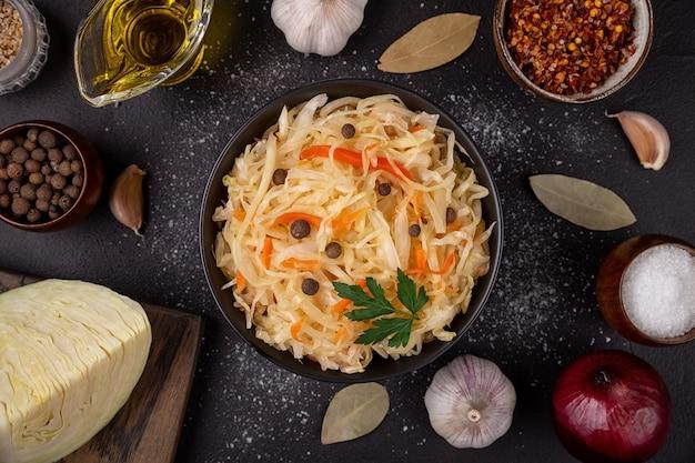 Tigela preta com chucrute azedo decorado com salsa e pimenta no plano de fundo escuro liso com repolho fresco de ingredientes, óleo, alho.