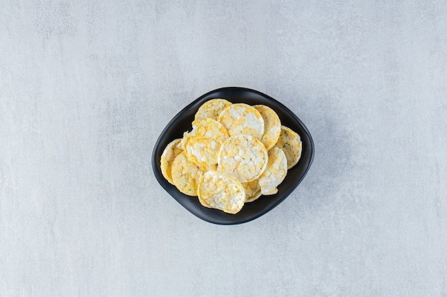 Tigela preta de deliciosas batatas fritas de arroz na pedra.