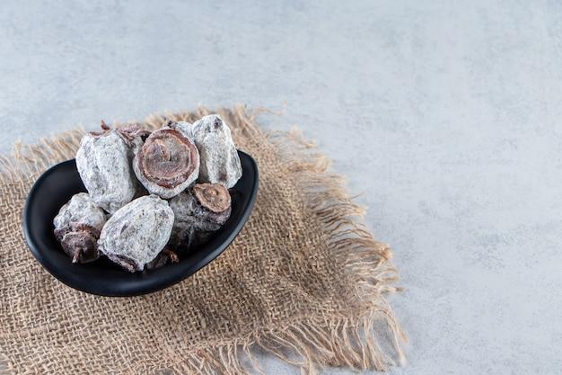 Tigela preta de frutas secas de caqui em fundo de mármore.