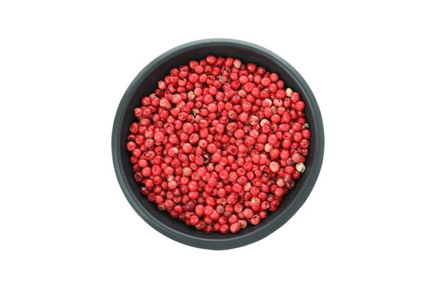 Tigela preta de grãos de pimenta vermelha isolada no fundo branco