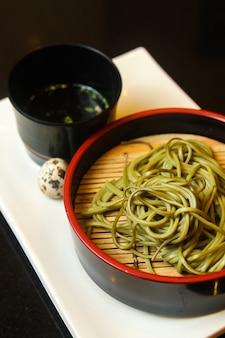 Tigela preta de macarrão verde com ovo de codorna e molho servido em uma bandeja branca