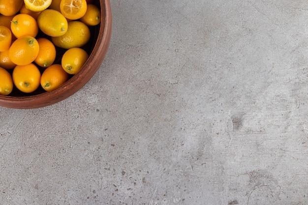 Tigela profunda de kumquats suculentos frescos em fundo de pedra.