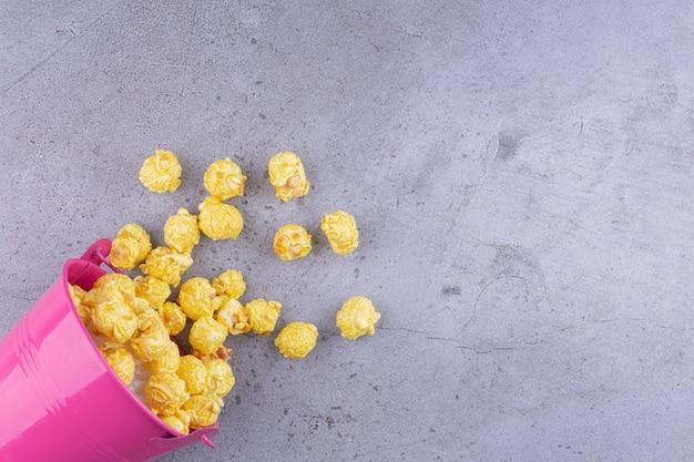 Tigela rosa com deliciosas bolinhas de milho na mesa de pedra