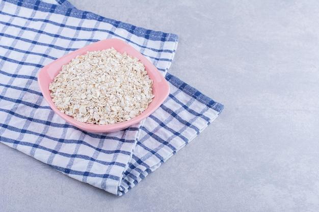 Tigela rosa em uma toalha, cheia de flocos de aveia, na superfície de mármore