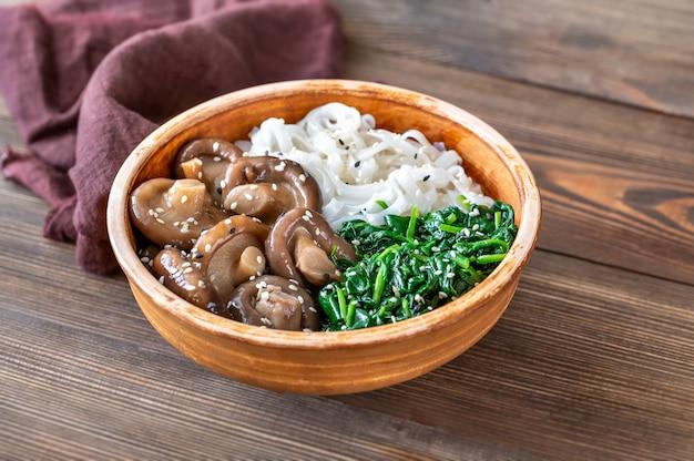 Tigela saudável com macarrão de arroz, shiitake marinado e espinafre cozido no vapor