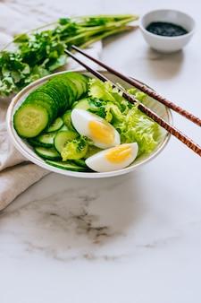 Tigela saudável, salada de pepino com ovos e coentro em fundo de mármore