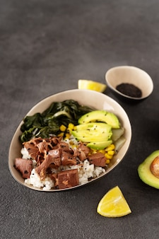 Tigela saudável vegan com arroz, salada e jaca no fundo escuro