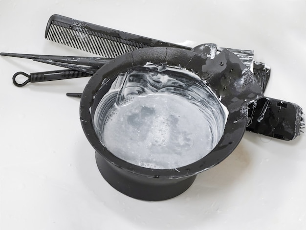 Tigela suja para misturar tintura de cabelo na pia. cabelo colorido.