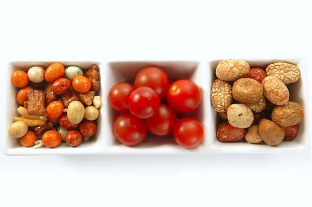 Tigela tripla com variados lanches japoneses e tomates