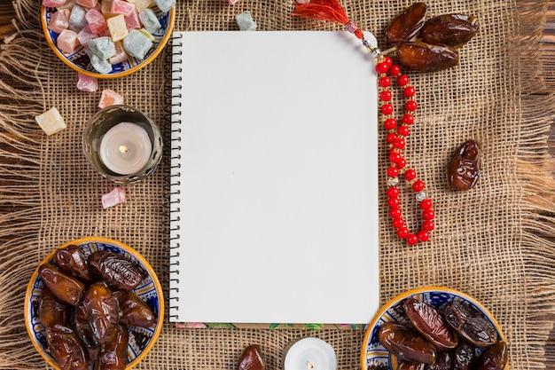 Tigela turca de datas suculentas; delícia lukum com página em branco e vermelho grânulos sagrados no pano de juta
