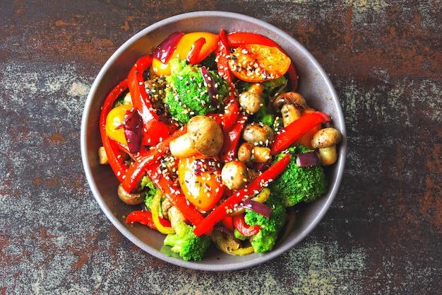 Tigela vegana com salada quente de vegetais e cogumelos. keto idéia do almoço. brócolis, pimentão, cogumelos. alimentos frescos e saudáveis, sem carne.