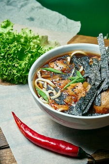 Tigela vegetariana com sopa de ramen, cogumelos shiitake, carne de soja em uma bandeja de madeira em uma composição com legumes frescos. comida saudável.