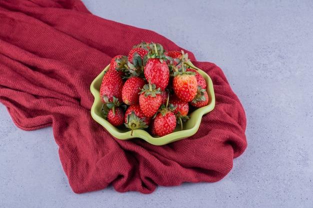 Tigela verde de morangos aninhada em uma pilha enrugada de toalha de mesa em fundo de mármore. foto de alta qualidade