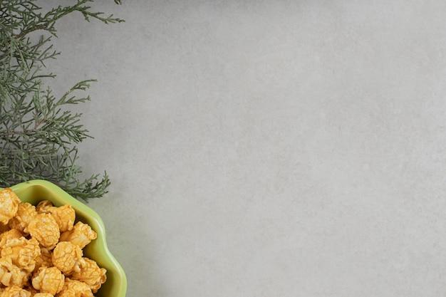 Tigela verde, folhas verdes e doces de pipoca em fundo de mármore.