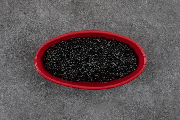 Tigela vermelha cheia de caviar preto na mesa cinza.