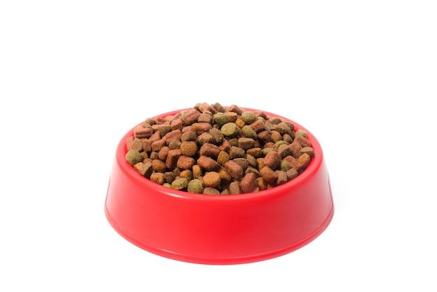 Tigela vermelha com ração animal seca para cães ou gatos.