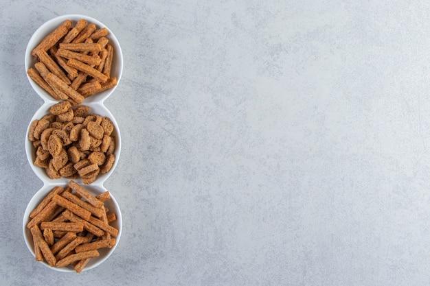 Tigelas brancas de saborosos biscoitos crocantes sobre fundo de pedra.