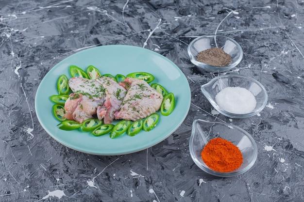 Tigelas cheias de especiarias diferentes ao lado do prato com asas e pimentas na superfície azul