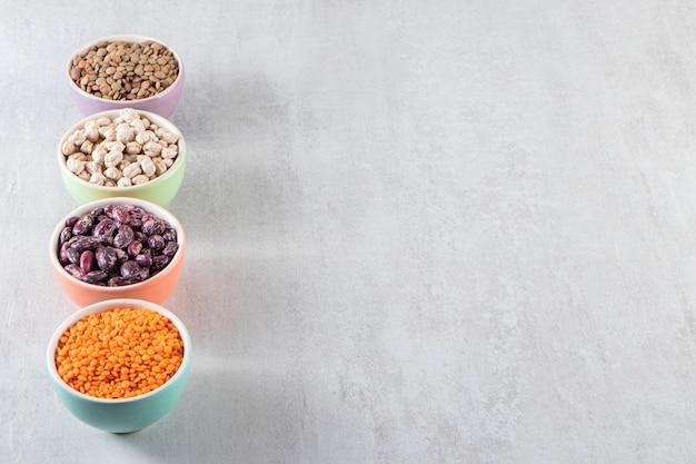 Tigelas coloridas cheias de lentilhas cruas, ervilhas e feijões na superfície da pedra