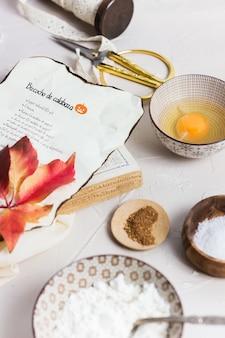 Tigelas com açúcar, ovo, farinha, castanhas e um livro de receitas com a receita de abóbora