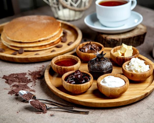 Tigelas com aperitivos na bandeja de madeira