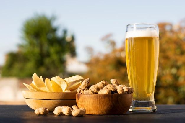 Tigelas com batatas fritas e amendoins, juntamente com copo de cerveja