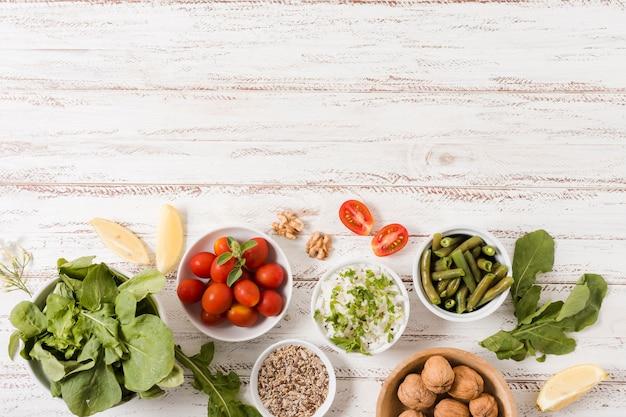 Tigelas com comida saudável em fundo de madeira
