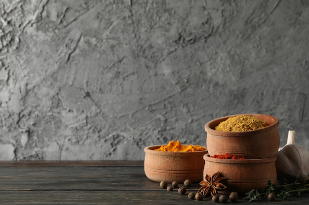 Tigelas com diferentes especiarias em pó e ingredientes em fundo de madeira, espaço para texto