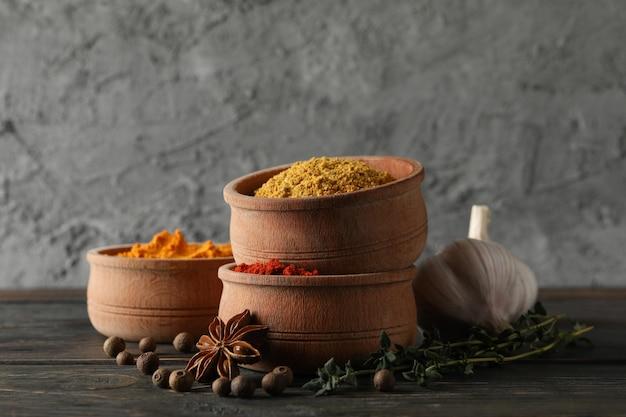 Tigelas com diferentes especiarias em pó e ingredientes na madeira, espaço para texto