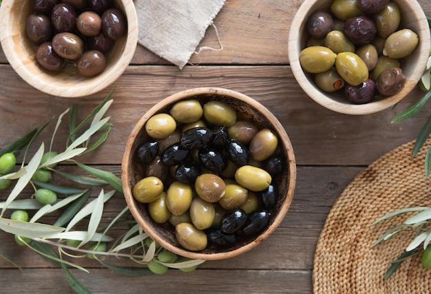 Tigelas com diferentes tipos de azeitonas: azeitonas pretas verdes kalamata com azeite