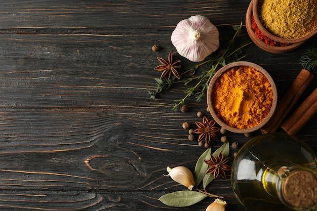 Tigelas com especiarias e ingredientes em fundo de madeira, espaço para texto