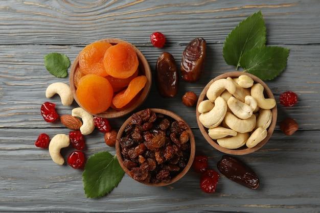Tigelas com frutas secas e nozes na mesa de madeira cinza