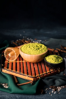 Tigelas com matcha verde na bandeja de madeira