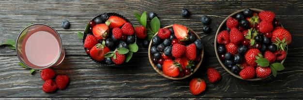 Tigelas com mistura de frutas vermelhas e suco em fundo de madeira