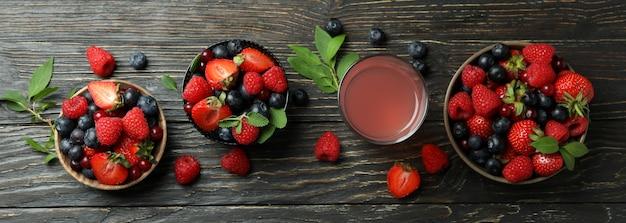 Tigelas com mistura de frutas vermelhas e suco em madeira Foto Premium