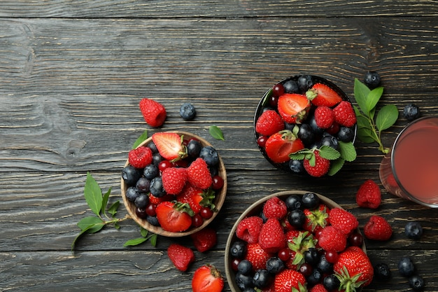 Tigelas com mistura de frutas vermelhas e suco em madeira