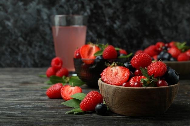 Tigelas com mistura de frutas vermelhas e suco na mesa de madeira