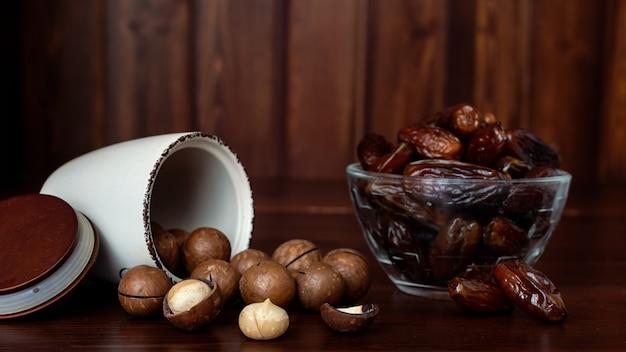 Tigelas com nozes de macadâmia e datas na mesa de madeira. conceito de frutas secas e nozes