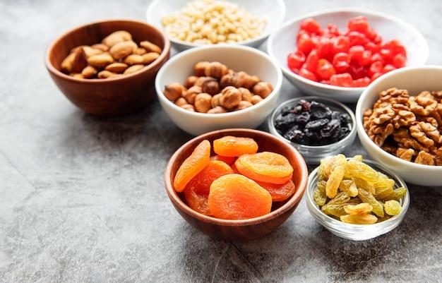 Tigelas com várias frutas secas e nozes em uma mesa de concreto cinza