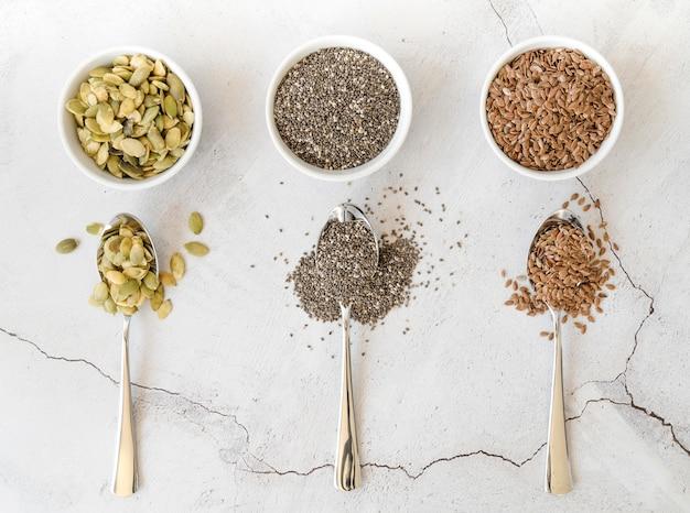 Tigelas com várias sementes e colheres