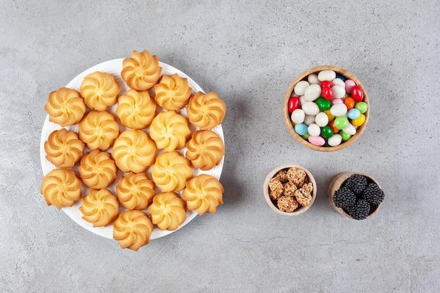 Tigelas de amoras, doces e biscoitos caseiros de amendoim em um prato com fundo de mármore. foto de alta qualidade