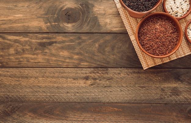 Tigelas de arroz crus diferentes no placemat sobre o fundo de madeira