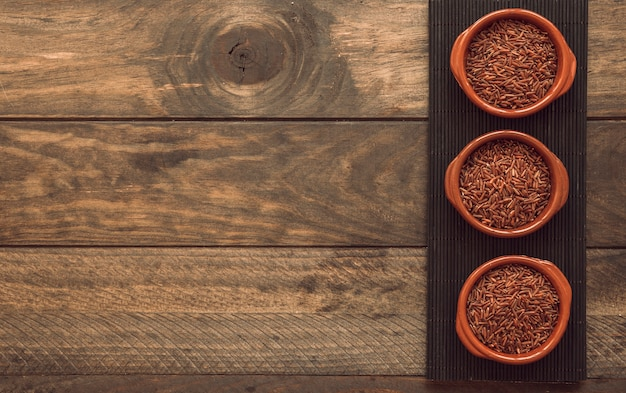 Tigelas de arroz jasmim vermelho cru no placemat sobre o fundo de madeira