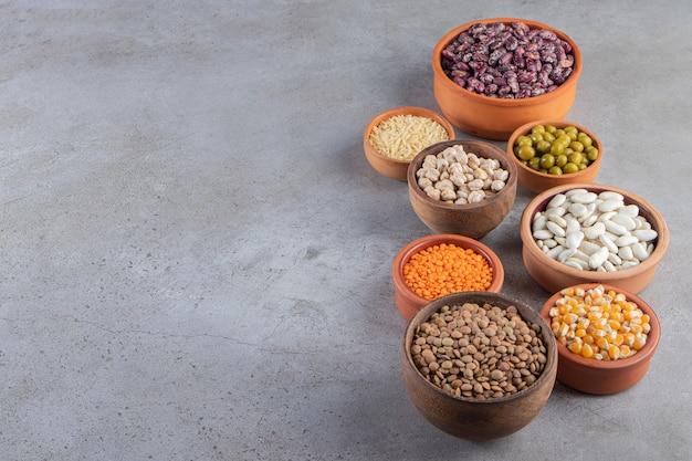 Tigelas de barro cheias de lentilha crua, ervilhas e feijão em fundo de pedra.